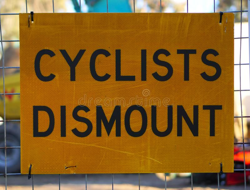 Close up view of Cyclists Dismount Signage. In yellow color stock photos