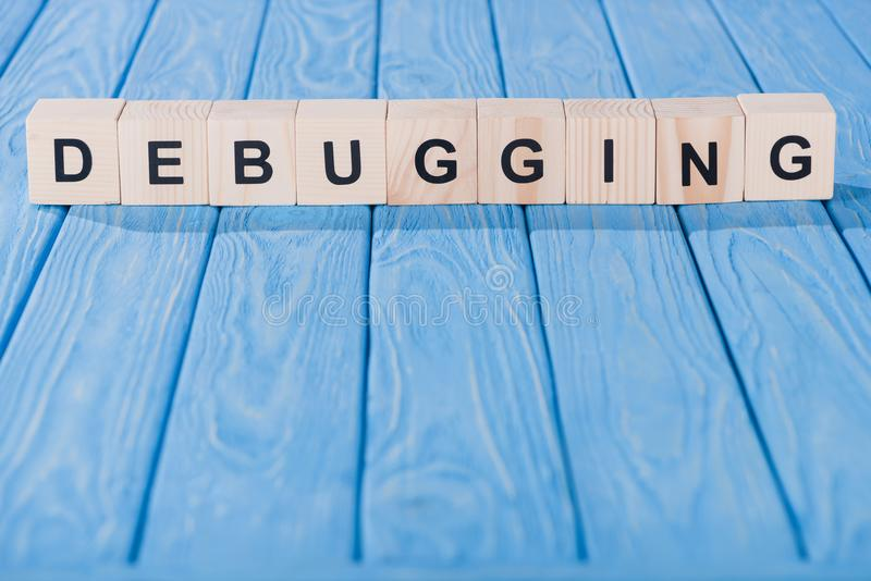 Close up view of debugging word made of wooden blocks. On blue tabletop royalty free stock photo