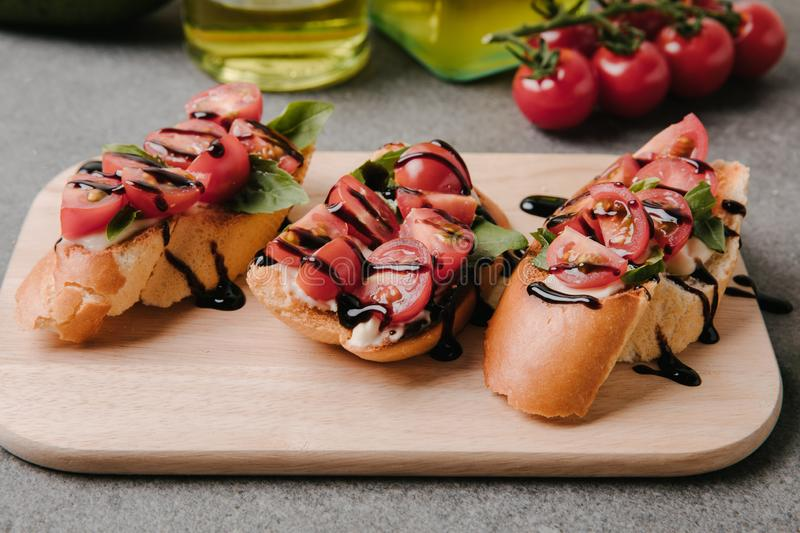 Close-up view of delicious bruschetta with tomatoes and balsamic on wooden board with ingredients royalty free stock images