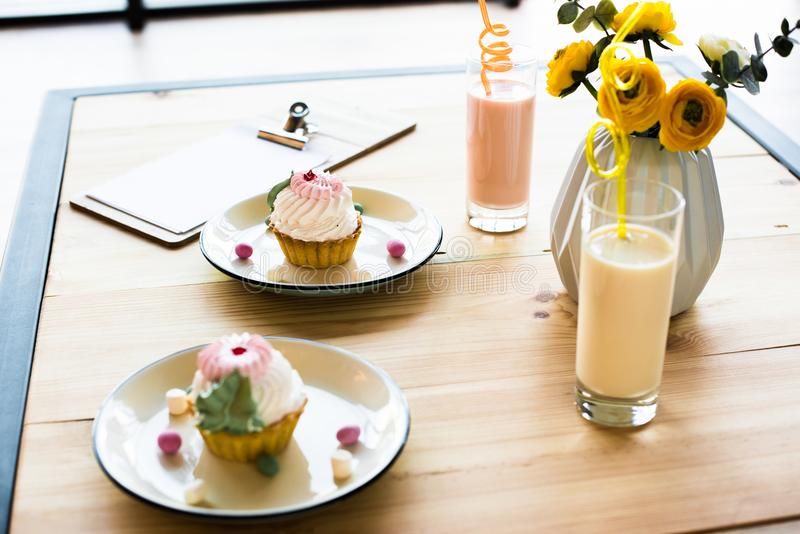 Close-up view of delicious cupcakes on plates and milkshakes in glasses on wooden table stock photos