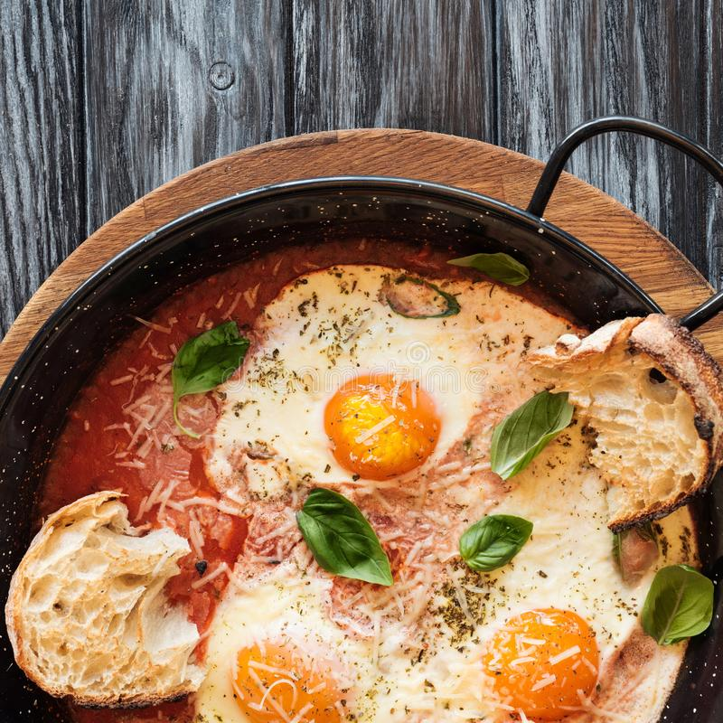 Close-up view of delicious fried eggs with cheese, bread and sauce in pan. On wooden table royalty free stock photos