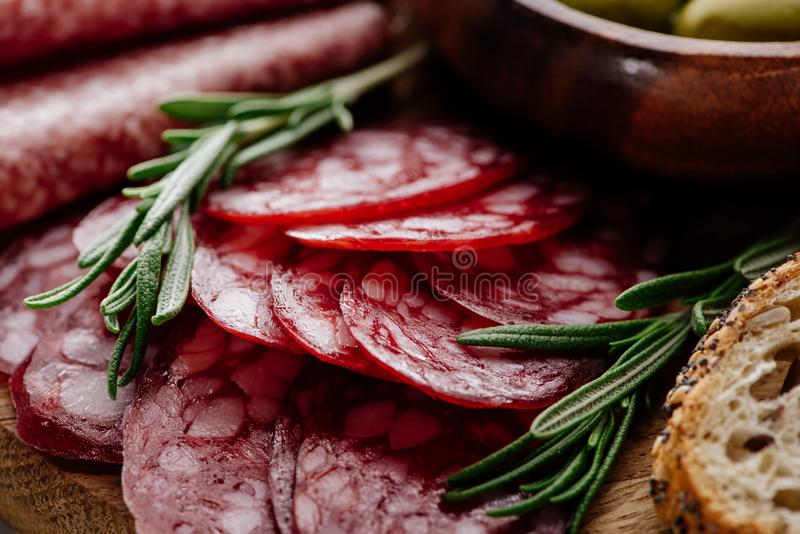 Close up view of delicious sliced salami with rosemary and bread on wooden. Cutting board royalty free stock photo