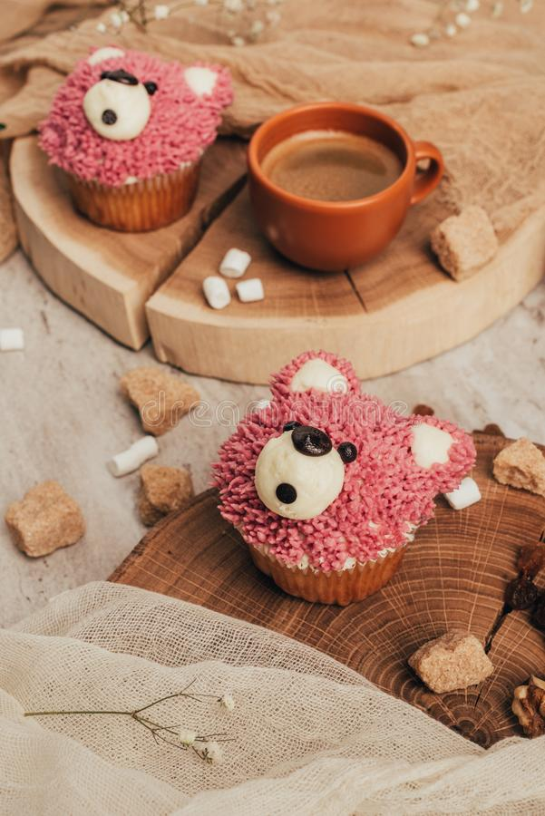 Close-up view of delicious sweet cupcakes in shape of bears and cup of coffee. On table stock photos