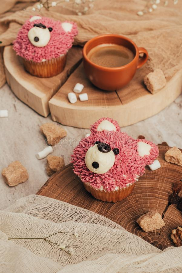 Close-up view of delicious sweet cupcakes in shape of bears and cup of coffee. On table royalty free stock images