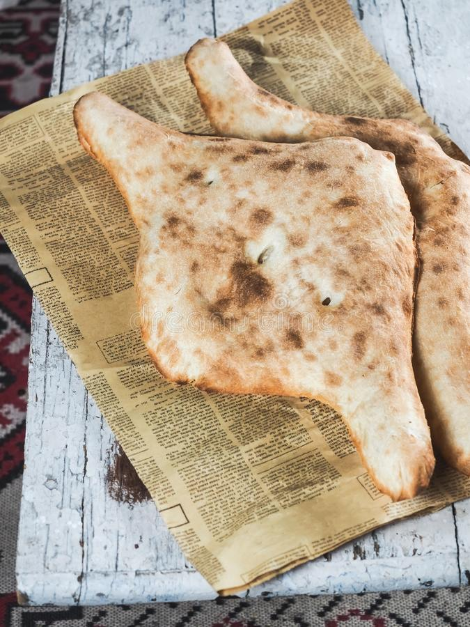 close-up view of delicious traditional georgian flatbreads on newspaper stock image