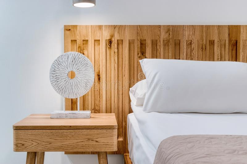 Close-up view of detail a bed in a bedroom with a lamp and side table. Home interior concept royalty free stock photos
