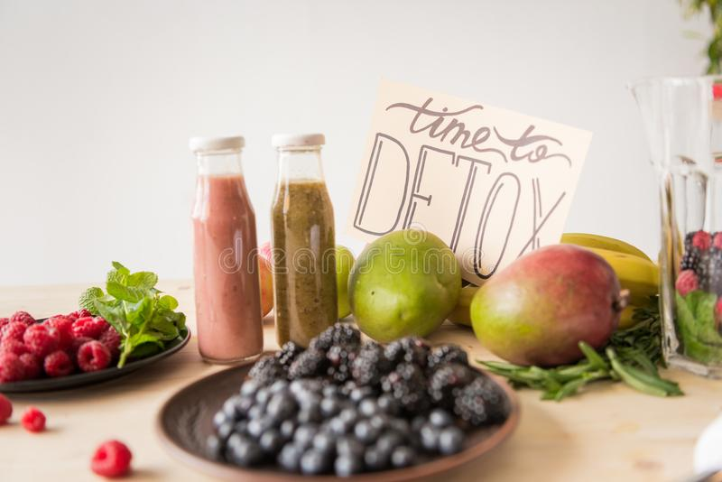 close up view of detox drinks, time to detox card and organic food stock illustration