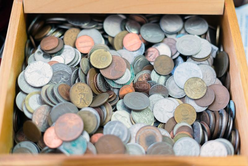 Close up view of different countries coins in a wooden box. Various metal coins background.  stock image