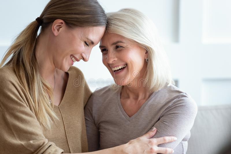 Closeup image aged mother and adult daughter touch foreheads laughing. Close up view different generations beautiful women, aged mother and adult daughter touch stock photo