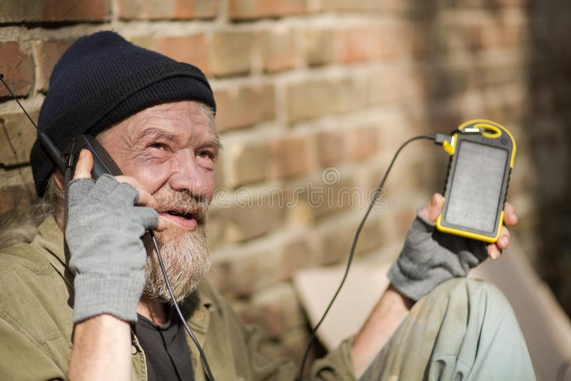 Close up view of dirrty tramp holding solar energy battery. Sunny day, homeless man charging phone from photovoltaic power station royalty free stock image