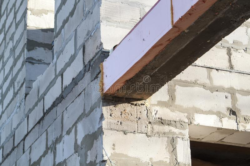 Close-up view of the docking concrete beam with a wooden log to the foam block wall of a country cottage under construction. Aerocrete, apartment, attic royalty free stock photo