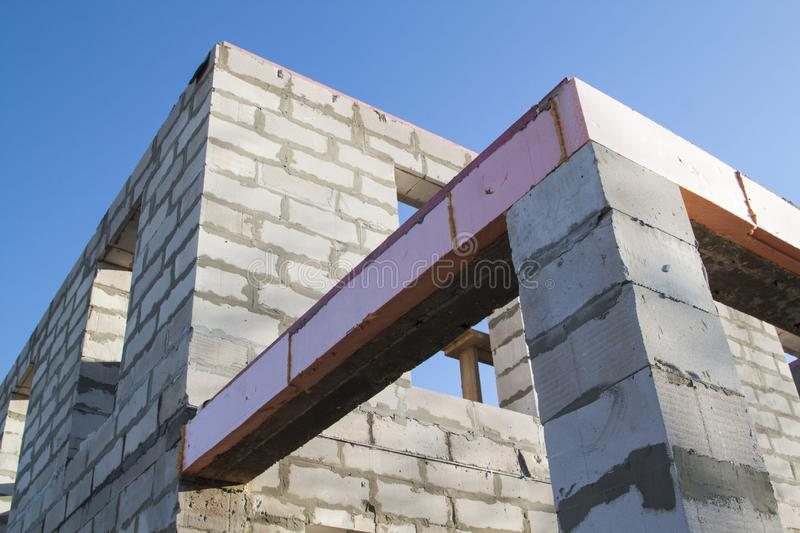 Close-up view of the docking concrete beam with a wooden log to the foam block wall of a country cottage under construction. Aerocrete, apartment, attic royalty free stock photos