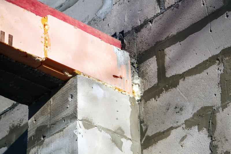 Close-up view of the docking concrete beam with a wooden log to the foam block wall of a country cottage under construction. Rafter, joist, installation, truss stock photos