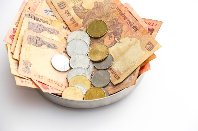 Donation plate with indian banknotes and coins on white background stock image