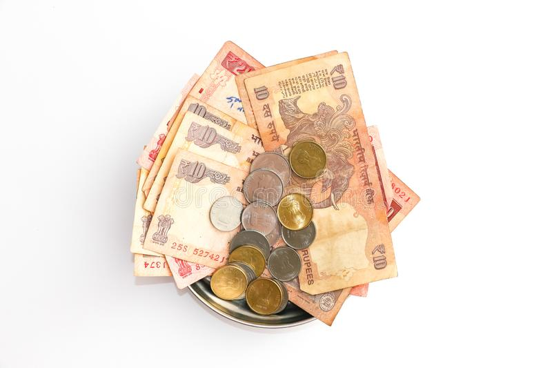 Donation plate with indian banknotes and coins on white background stock photos
