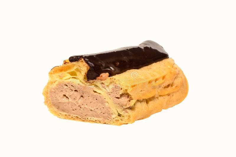 Close up view of eclair with cream. Cut in half filled profiterole with chocolate cream. royalty free stock images