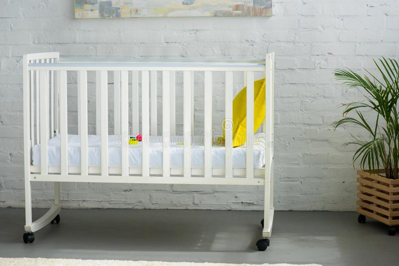 close up view of empty baby crib with yellow pillow royalty free stock photography