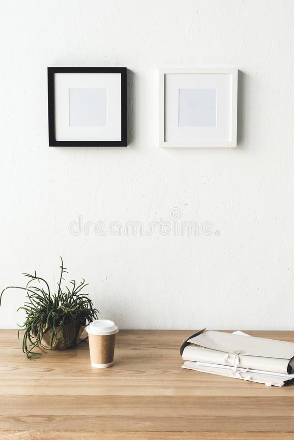 Close up view of empty photo frames hanging on wall at workplace with coffee to go. In room royalty free stock photography