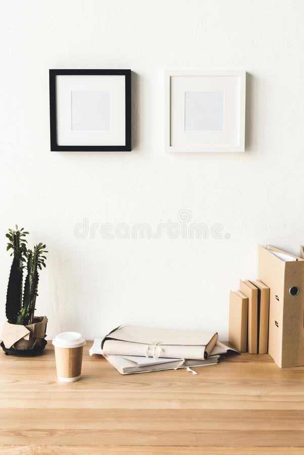 Close up view of empty photo frames hanging on wall at workplace with office supplies and coffee to go. In room stock photography