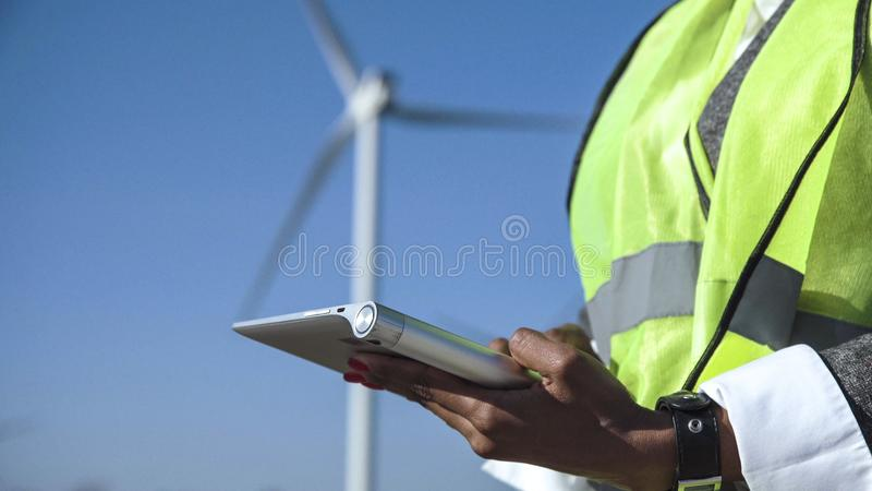 Engineer using digital tablet against wind turbine. Close up view of engineer working with digital tablet against wind turbine on sunny day stock images