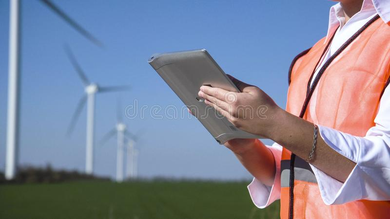 Engineer using digital tablet against wind turbine. Close up view of engineer working with digital tablet against wind turbine on sunny day stock photos