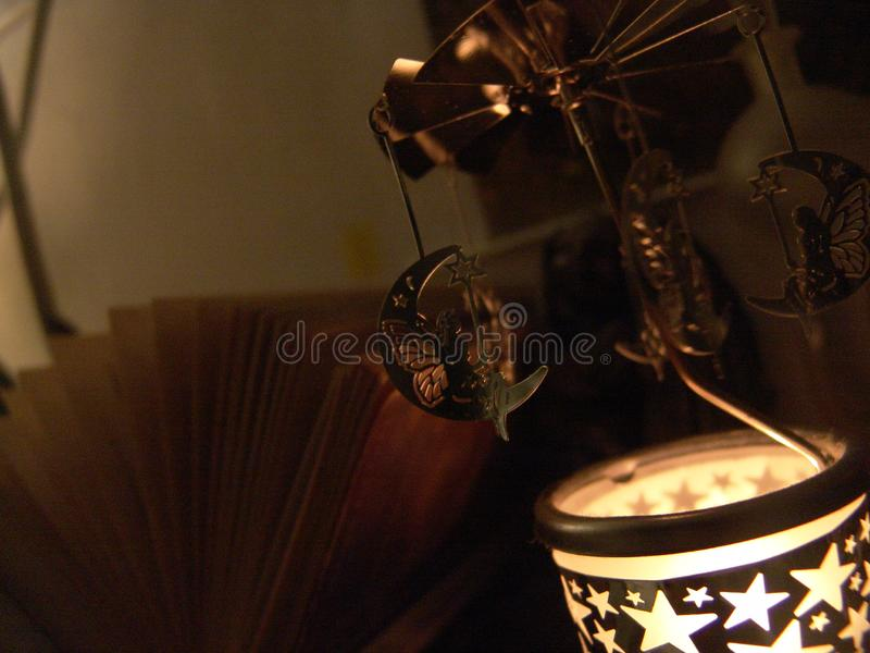 Close up view of a fairy sitting on a moon metal candle rotation carousel with stars shapes lit, in front of an open book , royalty free stock photo