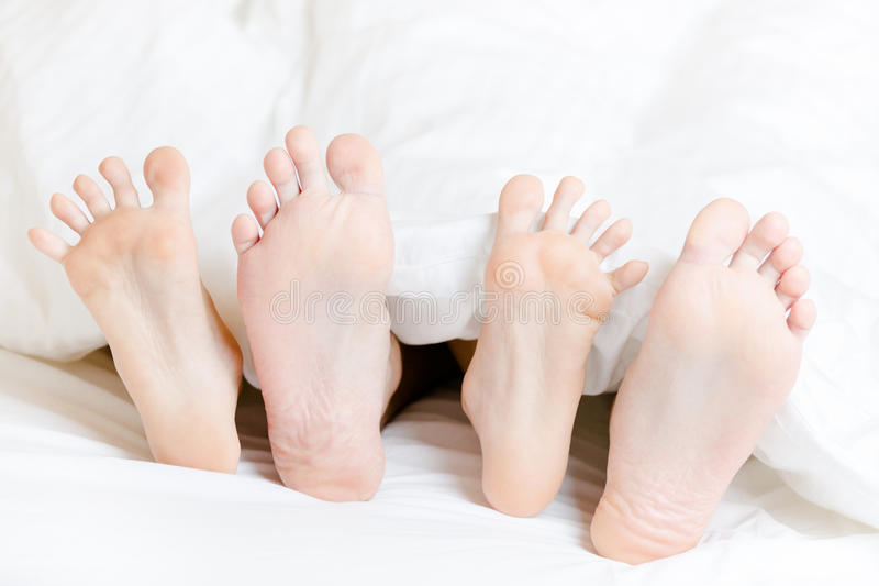 Download Close Up View Of Feet Of The Couple Lying In Bedroom Stock Photo - Image: 33408944