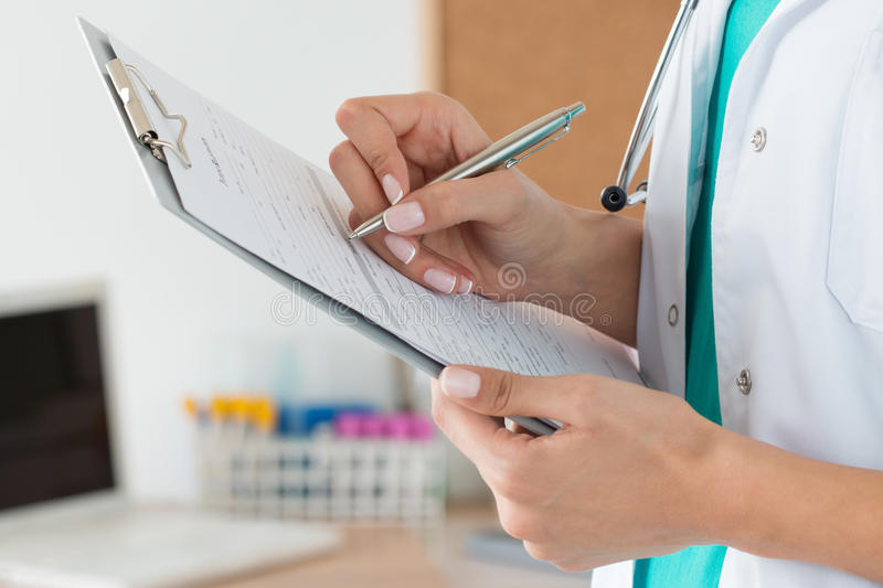 Close-up view of female doctor hands filling patient registration form stock photos