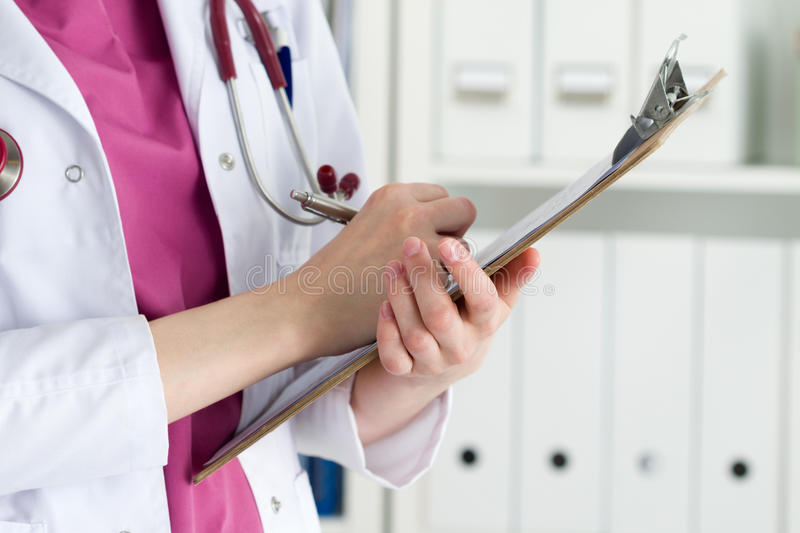 Close up view of female doctor hands holding clipping pad royalty free stock photography