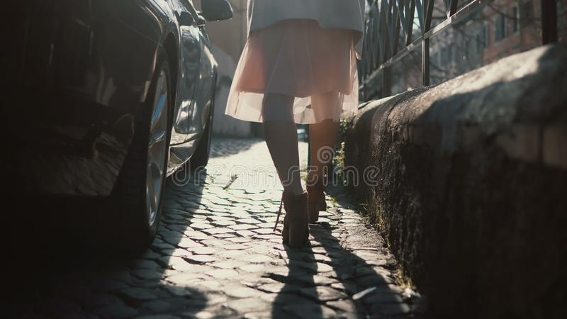 Close-up view of female feet walking through the urban street. Female in shoes and skirt going in the city centre. royalty free stock images
