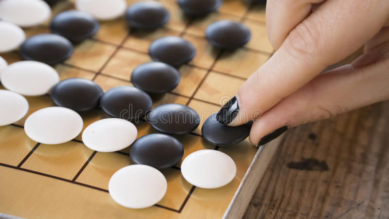 Close up view of female hand playing black and white stone pieces on Chinese go game board. Outside activity with natural sun light stock images