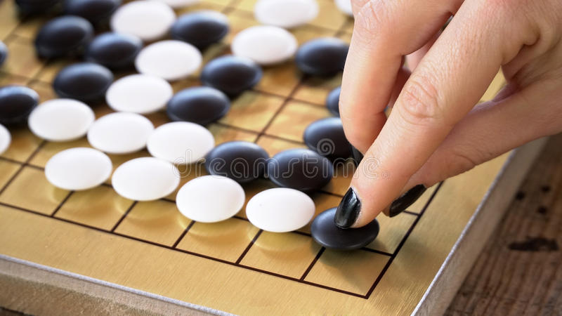Close up view of female hand playing black and white stone pieces on Chinese go game board. Outside activity with natural sun light royalty free stock photos