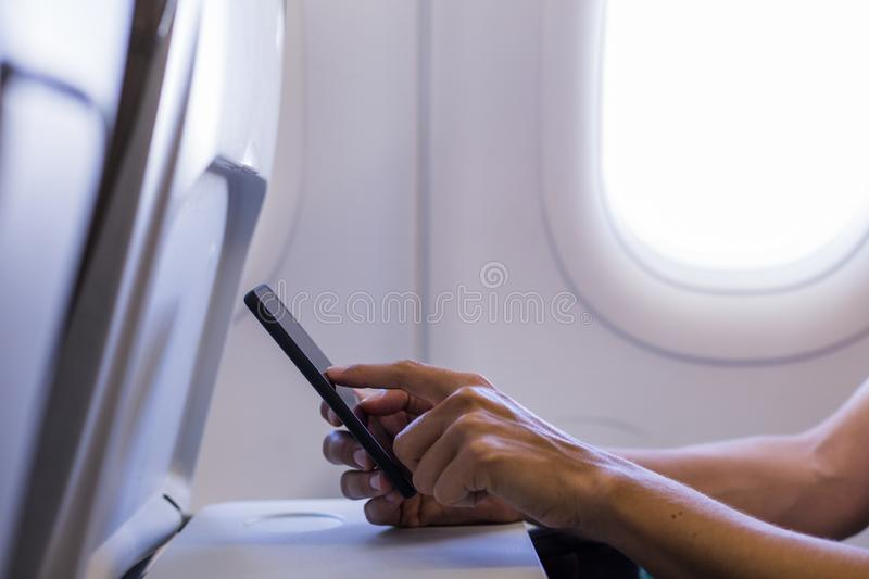 Close up view of female hands using a mobile phone in a plane. Travel concept. Display, read, tablet, journey, board, interior, person, window, corporate stock photo