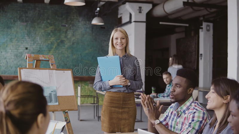 Close-up view of female manager walking through the office with documents. Multiracial team clap to businesswoman. royalty free stock images