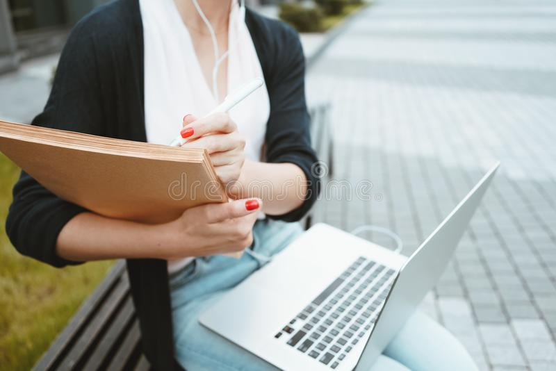 Close-up view on female student preparing for exams on outdoors in urban space, use laptop and paper documents. Business woman writes on paper royalty free stock photos