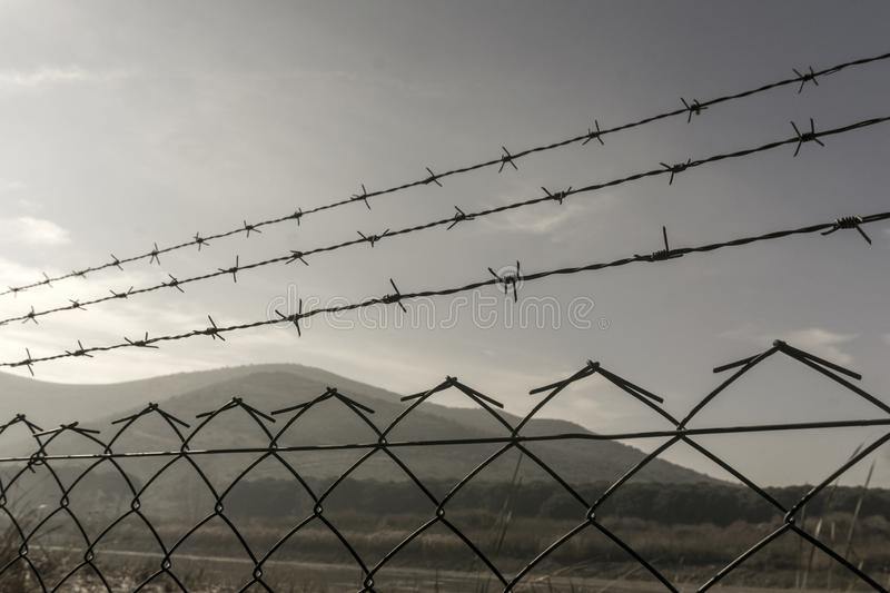 Prison fences with sky. Close up view of fences and wires stock photos