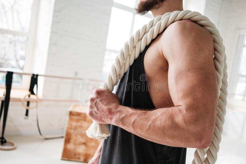 Close up view on fit sportsman with crossfit ropes in gym royalty free stock photo