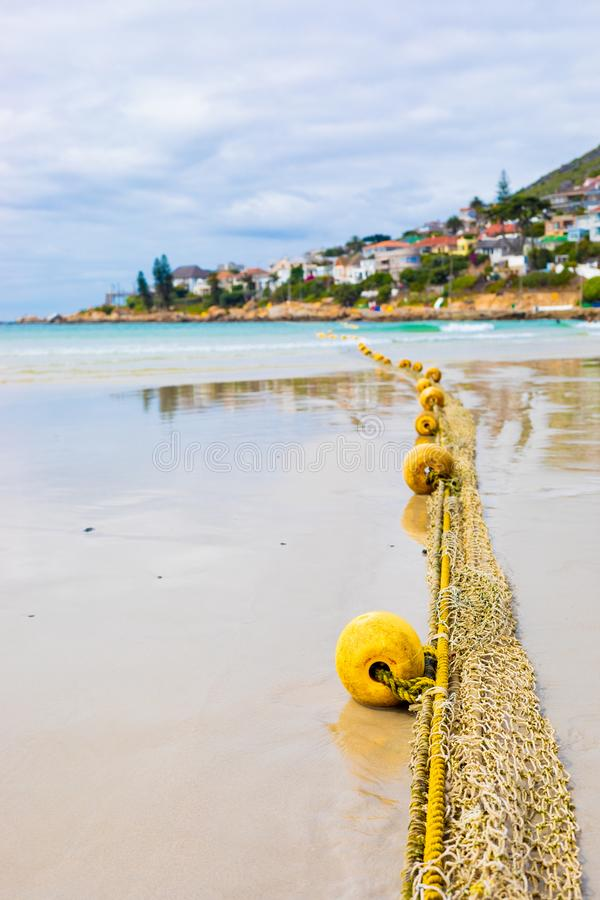 Close-up of fishing net on a sandy beach. Close-up view of a float of a traditional fishing net on a sandy beach stock image