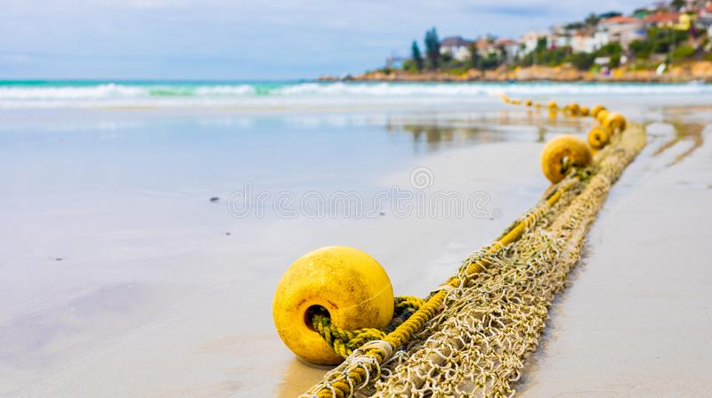 Close-up of fishing net on a sandy beach. Close-up view of a float of a traditional fishing net on a sandy beach stock photography