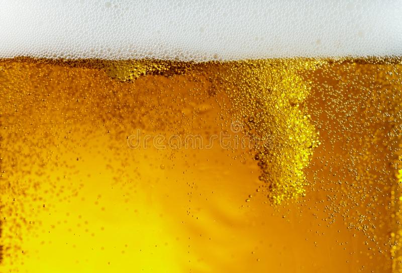 Close up view of floating bubbles in light beer texture. Close up view of floating bubbles in light golden colored beer background. Texture of cooling summer`s royalty free stock photo
