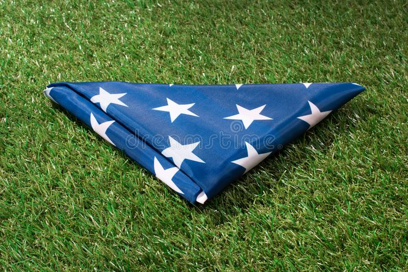 Close up view of folded american flag on green lawn, americas independence. Day concept stock photos