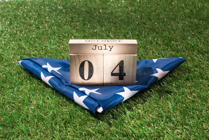 Close up view of folded american flag and wooden calendar with 4th july date on green lawn, americas independence. Day concept stock photos