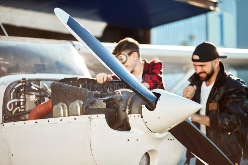 Close up view on fore body of propeller airplane, blurred dad and son standing behind royalty free stock photography