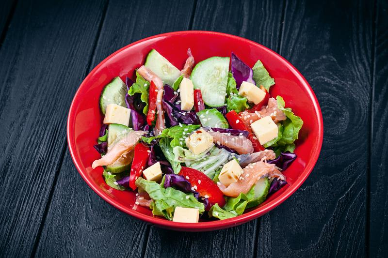 Close up view on fresh homemade salad with salmon, tomato, cucumber, lettuce and cheese. Healthy food. Seafood for lunch. Copy stock images