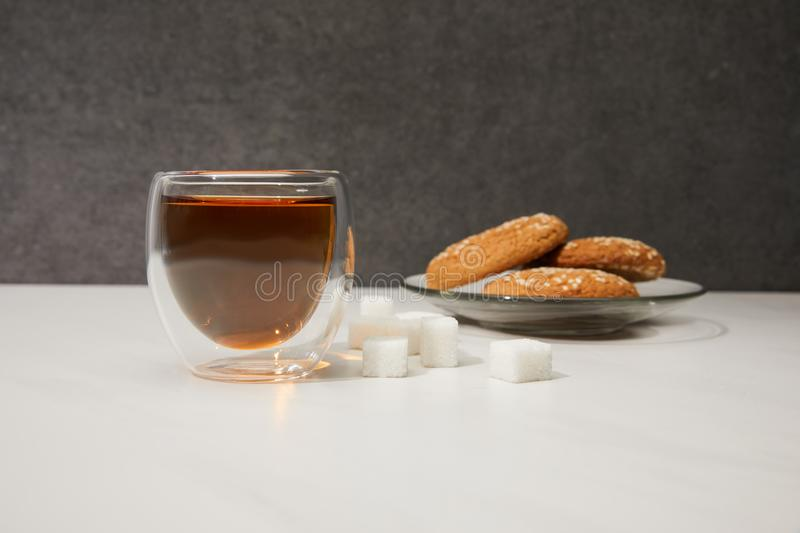 Close-up view of fresh hot tea in glass cup, sugar cubes and tasty cookies on grey royalty free stock photos