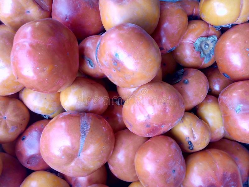 Close up view of fresh organic reddish persimmon arranged in fruit basket. Organic persimmon arranged in fruit basket royalty free stock photo