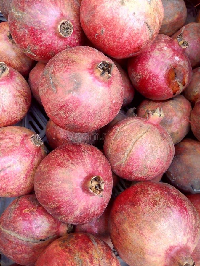 Close up view of fresh organic reddish pomegranate arraged in fruit basket. Red pomegranates arranged in fruit basket royalty free stock image