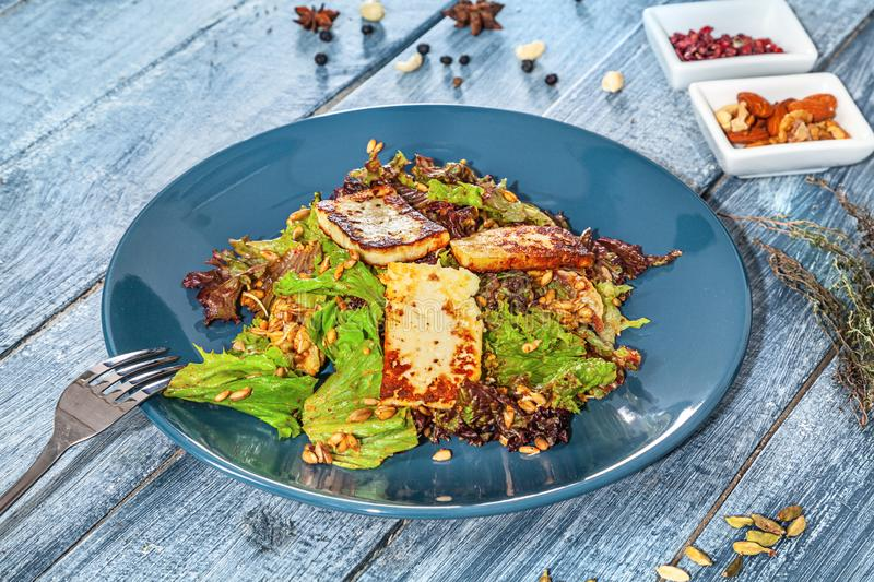 Close up view on fresh vegan salad with cheese on blue wooden background with herbs and spices. Copy space for design. Healthy stock photos