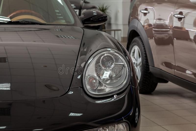 Close-up view of the front of a black sports car in a coupe with a transparent round headlight in the dealership at the exhibition stock images