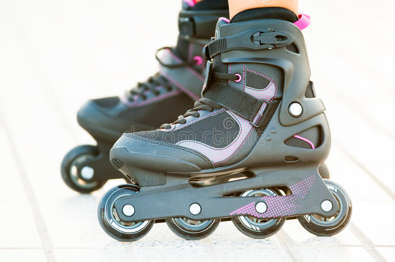 Close-up view of girl's legs in roller blades royalty free stock photo